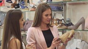 Δύο θηλυκοί φίλοι εξετάζουν το μπεζ παπούτσι στο κατάστημα απόθεμα βίντεο