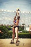 Δύο θηλυκοί φορείς πετοσφαίρισης παραλιών ανταγωνίζονται για τη σφαίρα καθαρός Στοκ Εικόνες