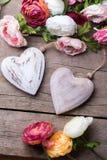 Δύο διακοσμητικά άσπρα ξύλινα καρδιές και λουλούδια Στοκ εικόνα με δικαίωμα ελεύθερης χρήσης
