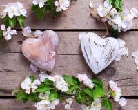 Δύο διακοσμητικά καρδιές και λουλούδια δέντρων μηλιάς εκλεκτής ποιότητας σε ξύλινο Στοκ Φωτογραφίες