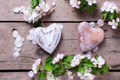 Δύο διακοσμητικά καρδιές και λουλούδια δέντρων μηλιάς εκλεκτής ποιότητας σε ξύλινο Στοκ Φωτογραφία