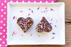Δύο διαμορφωμένα καρδιά κομμάτια κέικ σοκολάτας στο άσπρο πιάτο Στοκ Φωτογραφίες