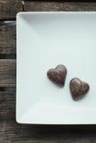 Δύο διαμορφωμένες καρδιά πραλίνες σοκολάτας σε ένα άσπρο πιάτο και ξύλινος Στοκ φωτογραφία με δικαίωμα ελεύθερης χρήσης