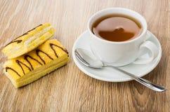 Δύο κέικ με τη βουτύρου κρέμα, το φλυτζάνι του τσαγιού και το κουταλάκι του γλυκού Στοκ φωτογραφία με δικαίωμα ελεύθερης χρήσης