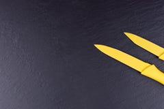 Δύο κίτρινα μαχαίρια κουζινών στο μαύρο πιάτο πλακών Στοκ φωτογραφία με δικαίωμα ελεύθερης χρήσης