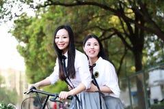 Δύο καλά ασιατικά κινεζικά όμορφα κορίτσια φορούν το κοστούμι σπουδαστών στο οδηγώντας ποδήλατο γέλιου χαμόγελου σχολικών καλύτερ Στοκ εικόνες με δικαίωμα ελεύθερης χρήσης