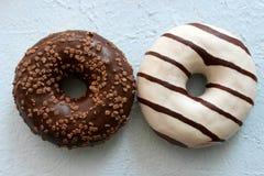 Δύο καλυμμένα με σοκολάτα doughnuts που απομονώνονται στοκ εικόνα με δικαίωμα ελεύθερης χρήσης