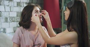 Δύο καλύτεροι φίλοι στις κυρίες πρωινού έχουν μια ρουτίνα ομορφιάς που παίρνει φρεσκότερη τεθειμένη στα πρόσωπα τα eyepatches απόθεμα βίντεο