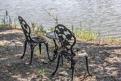 Δύο καρέκλες επεξεργασμένου σιδήρου και ένας πίνακας κατά μήκος μιας ακτής του Ντελαγουέρ Στοκ εικόνες με δικαίωμα ελεύθερης χρήσης