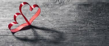 Δύο καρδιές κορδελλών στο ξύλο Στοκ Εικόνες