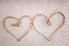 Δύο καρδιές αγάπης φιαγμένες από σειρά που διασχίζεται μαζί στο ύφασμα Στοκ Εικόνες
