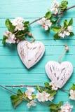 Δύο καρδιές και λουλούδια δέντρων μηλιάς στο τυρκουάζ ξύλινο backgroun Στοκ φωτογραφία με δικαίωμα ελεύθερης χρήσης