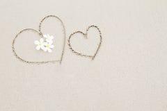 Δύο καρδιές με τα άσπρα λουλούδια στο υπόβαθρο επιφάνειας παραλιών Στοκ Εικόνες