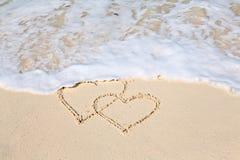Δύο καρδιές που επισύρονται την προσοχή στην άμμο παραλιών, παραμερίζουν το σκούπισμα των καρδιών Στοκ Φωτογραφίες