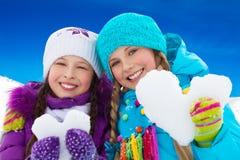 Δύο καρδιές χιονιού εκμετάλλευσης πορτρέτου κοριτσιών Στοκ Φωτογραφία