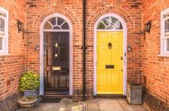 Δύο κατοικημένες μπροστινές πόρτες, ένας Μαύρος ένας κίτρινοι και ένα κόκκινο bric στοκ εικόνες