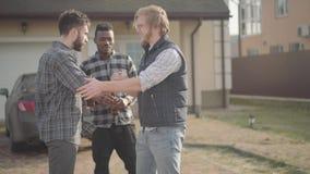 Δύο καυκάσια και άτομα αφροαμερικάνων που στέκονται μπροστά από τη με απόθεμα βίντεο