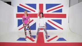 Δύο καυκάσια χαμογελώντας θηλυκά κάνουν την πρακτική χορού στο υπόβαθρο της βρετανικής σημαίας φιλμ μικρού μήκους