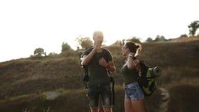 Δύο καυκάσια trevellers που παίρνουν το υπόλοιπο σε έναν λόφο κατά τη διάρκεια της πεζοπορίας τους Πάρτε των σακιδίων πλάτης και  απόθεμα βίντεο