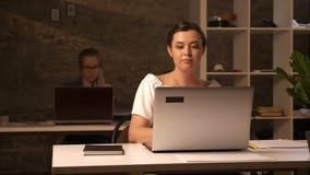 Δύο καυκάσιες επιχειρηματίες κάθονται το ένα μετά το άλλο και εργάζονται στα lap-top εσωτερικά, καφετί στούντιο τούβλου απόθεμα βίντεο