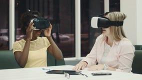 Δύο καυκάσιες και αφροαμερικανίδες γυναίκες που χρησιμοποιούν τα γυαλιά εικονικής πραγματικότητας φιλμ μικρού μήκους