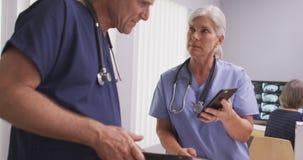 Δύο καυκάσιες ώριμες γιατροί ή νοσοκόμες στις συσκευές τεχνολογίας Στοκ φωτογραφίες με δικαίωμα ελεύθερης χρήσης