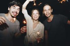Δύο καυκάσιοι άνδρες και μια γυναίκα που παίζει με τον εορτασμό sparklers και την εορταστική έννοια κομμάτων Στοκ Φωτογραφίες