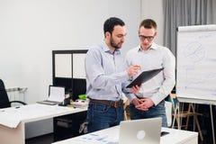 Δύο καυκάσιοι διοικητικοί συνεργάτες στην περιστασιακή ένδυση που διοργανώνει μια επιχειρησιακή συζήτηση στην αρχή Στοκ Φωτογραφία