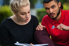 Δύο καυκάσιοι σπουδαστές που διαβάζουν ένα βιβλίο στο πάρκο Στοκ Εικόνες