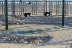 Δύο κενά καθίσματα ταλάντευσης μωρών στο αμμώδες πάρκο στοκ εικόνες