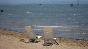 Δύο κενές πλαστικές καρέκλες στην παραλία απόθεμα βίντεο