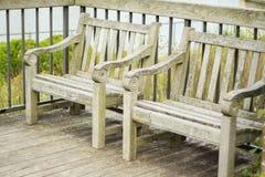Δύο κενοί παλαιοί ξύλινοι πάγκοι που κάθονται σε Patio που αγνοεί τη λίμνη κήπων Στοκ Φωτογραφία