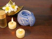 Δύο κεριά, ένα χρυσό πιάτο σχεδίων, και aromatherapy μπουκάλι Στοκ Εικόνες
