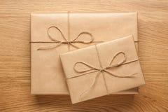 Δύο κιβώτια δώρων που τυλίγονται στο έγγραφο του Κραφτ για τον ξύλινο πίνακα στοκ φωτογραφίες