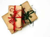 Δύο κιβώτια δώρων Χριστουγέννων που συσκευάζονται στον Κραφτ και τις κόκκινες και πράσινες κορδέλλες σε ένα άσπρο υπόβαθρο στοκ εικόνες