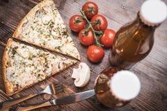 Δύο κομμάτια πίτσας, δύο μπουκαλιών της μπύρας, των ντοματών κερασιών και champignons Στοκ Εικόνες