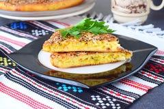 Δύο κομμάτια της πίτας άσπρων λάχανων με το καρότο σε ένα μαύρο πιάτο με το φλυτζάνι του τσαγιού και το υπόλοιπο της πίτας σε ένα Στοκ φωτογραφία με δικαίωμα ελεύθερης χρήσης