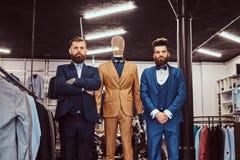 Δύο κομψά ντυμένοι βοηθοί καταστημάτων που θέτουν κοντά στο μανεκέν στο menswear κατάστημα στοκ φωτογραφία