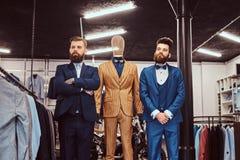 Δύο κομψά ντυμένοι βοηθοί καταστημάτων που θέτουν κοντά στο μανεκέν στο menswear κατάστημα στοκ εικόνες