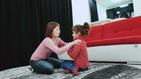 Δύο κορίτσια, ένα από τα με το κάτω σύνδρομο, που κάθεται στον τάπητα στο σπίτι, παιχνίδι και έχουν τη διασκέδαση απόθεμα βίντεο