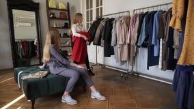 Δύο κορίτσια ή δίδυμες αδελφές που ψωνίζουν μαζί: το μακρυμάλλες νέο ξανθό θηλυκό δοκιμάζει ένα νέο κόκκινο παλτό στεμένος απόθεμα βίντεο