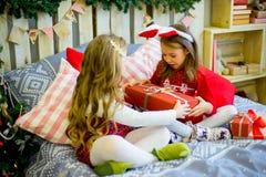 Δύο κορίτσια δίνουν τα δώρα Χριστουγέννων Στοκ Εικόνες