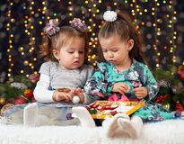 Δύο κορίτσια ανοίγουν τα δώρα στη διακόσμηση Χριστουγέννων, το σκοτεινό υπόβαθρο με το φωτισμό και boke τα φω'τα, έννοια χειμεριν Στοκ φωτογραφίες με δικαίωμα ελεύθερης χρήσης