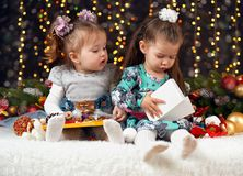 Δύο κορίτσια ανοίγουν τα δώρα στη διακόσμηση Χριστουγέννων, το σκοτεινό υπόβαθρο με το φωτισμό και boke τα φω'τα, έννοια χειμεριν Στοκ εικόνες με δικαίωμα ελεύθερης χρήσης