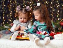 Δύο κορίτσια ανοίγουν τα δώρα στη διακόσμηση Χριστουγέννων, το σκοτεινό υπόβαθρο με το φωτισμό και boke τα φω'τα, έννοια χειμεριν Στοκ Εικόνες