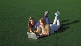 Δύο κορίτσια βρίσκονται στο χορτοτάπητα με τη χλόη χρησιμοποιώντας το lap-top HD απόθεμα βίντεο