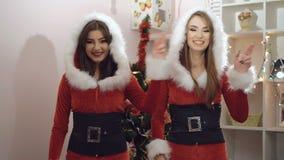 Δύο κορίτσια γοητείας έντυσαν στο κοστούμι santa που χορεύει και που φλερτάρει εσωτερικό 4K απόθεμα βίντεο