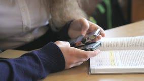 Δύο κορίτσια εξετάζουν τις φωτογραφίες χρησιμοποιώντας τα κινητά τηλέφωνα απόθεμα βίντεο