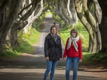 Δύο κορίτσια επισκέπτονται τους σκοτεινούς φράκτες στο ταξίδι τους μέσω της βόρειας Ιρλανδίας στοκ φωτογραφία