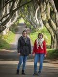Δύο κορίτσια επισκέπτονται τους σκοτεινούς φράκτες στο ταξίδι τους μέσω της βόρειας Ιρλανδίας στοκ εικόνα με δικαίωμα ελεύθερης χρήσης
